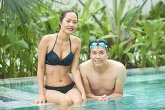 Asiatiska par i simbassäng arkivfoto