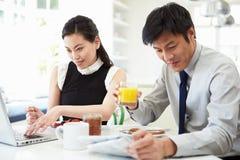 Asiatiska par med bärbara datorn och tidningen på frukosten Arkivbild