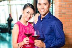Asiatiska par med exponeringsglas av rött vin Arkivfoton