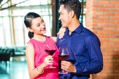 Asiatiska par med exponeringsglas av rött vin Royaltyfria Foton
