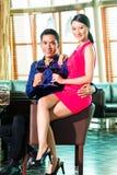Asiatiska par med exponeringsglas av rött vin Royaltyfri Foto