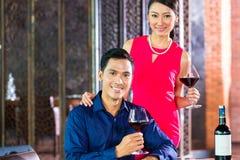 Asiatiska par med exponeringsglas av rött vin Fotografering för Bildbyråer