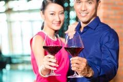 Asiatiska par med exponeringsglas av rött vin Arkivbilder