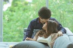 Asiatiska par med romantiskt ögonblick för förälskelse och kopplar av på soffan i en mo royaltyfri bild