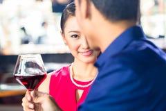 Asiatiska par med vin i restaurang Royaltyfri Foto