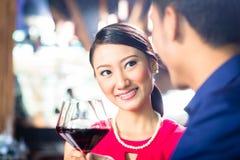 Asiatiska par med vin i restaurang Royaltyfria Foton