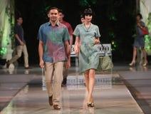 Asiatiska par modellerar bärande batik på modeshowlandningsbanan Royaltyfria Bilder