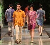 Asiatiska par modellerar bärande batik på modeshowlandningsbanan Royaltyfri Bild