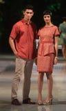 Asiatiska par modellerar bärande batik på modeshowlandningsbanan Arkivbild