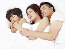 Asiatiska par och barn som sover i säng Royaltyfri Foto