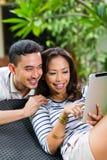 Asiatiska par som är utomhus- med en minnestavlaPC Arkivfoto