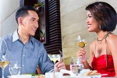 Asiatiska par som äter middag fint i restaurang Arkivbilder