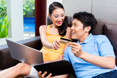 Asiatiska par som direktanslutet shoppar i internet med bärbara datorn Royaltyfria Bilder