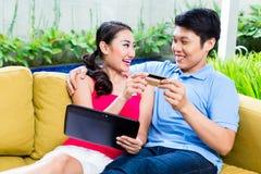Asiatiska par som direktanslutet shoppar i internet med bärbara datorn Arkivfoton