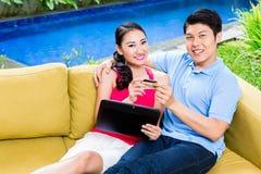 Asiatiska par som direktanslutet shoppar i internet med bärbara datorn Royaltyfri Bild