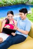 Asiatiska par som direktanslutet shoppar i internet med bärbara datorn Fotografering för Bildbyråer
