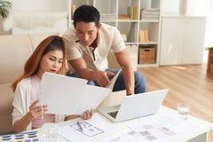 Asiatiska par som diskuterar lägenhetplan arkivbild