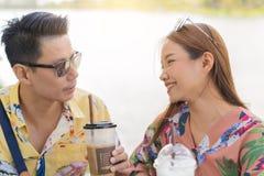 Asiatiska par som dricker kaffe och smileing på flodbakgrund Arkivbild