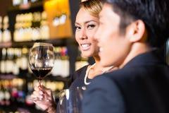 Asiatiska par som dricker rött vin Royaltyfri Fotografi