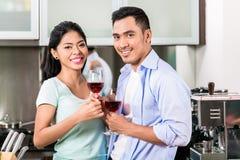 Asiatiska par som dricker rött vin i kök Arkivfoton