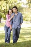 Asiatiska par som går handen - in - handen parkerar in Arkivbild