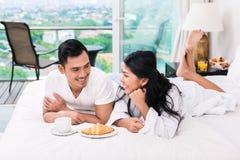 Asiatiska par som har frukosten i säng Royaltyfri Bild