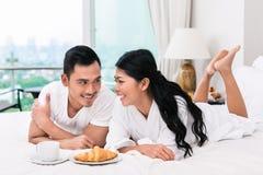 Asiatiska par som har frukosten i säng Arkivfoto