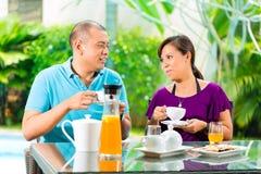 Asiatiska par som har kaffe på den hem- farstubron Royaltyfri Fotografi