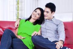 Asiatiska par som hemma kopplar av på en röd soffa fotografering för bildbyråer