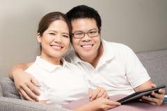 Asiatiska par som kopplar av på soffan Royaltyfri Fotografi