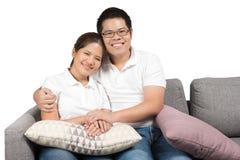 Asiatiska par som kopplar av på soffan Arkivbild