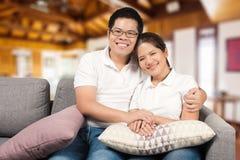 Asiatiska par som kopplar av på soffan Arkivfoton