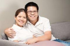 Asiatiska par som kopplar av på soffan Arkivbilder