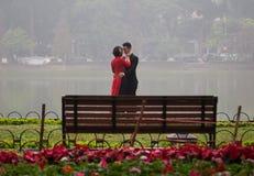 Asiatiska par som kramar och kysser i en härlig utomhus- sikt Fotografering för Bildbyråer
