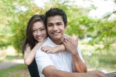 asiatiska par som kramar parken Royaltyfri Bild
