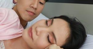 Asiatiska par som ligger på säng, mankysskvinnas kind stock video