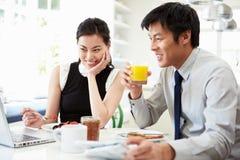 Asiatiska par som ser bärbara datorn över frukosten Royaltyfri Fotografi
