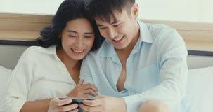Asiatiska par som spelar leken vid smartphonen tillsammans