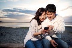 asiatiska par som texting Arkivfoton
