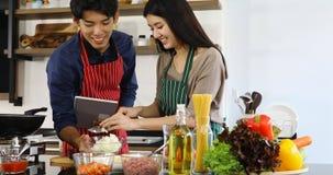Asiatiska par som tillsammans lagar mat mål i kök arkivfilmer