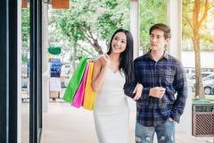 Asiatiska par som tycker om romanska utgiftershoppingpåsar, danar sho Royaltyfria Bilder