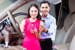 Asiatiska par som väljer den lyxiga bilen i återförsäljare Royaltyfri Bild