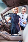 Asiatiska par som väljer den lyxiga bilen i återförsäljare Royaltyfria Foton
