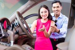 Asiatiska par som väljer den lyxiga bilen i återförsäljare Arkivfoto