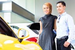 Asiatiska par som väljer roadsterbilen i återförsäljare Fotografering för Bildbyråer