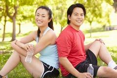 Asiatiska par som vilar efter övning Arkivfoton
