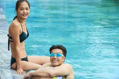 Asiatiska par som vilar i simbassäng royaltyfri fotografi