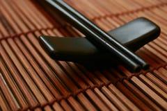 asiatiska pinnar som äter middag hållareseten Arkivbild