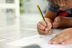 Asiatiska pojkar skriver på golvet arkivfoton