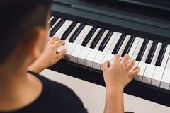 Asiatiska pojkar som spelar pianot royaltyfria bilder